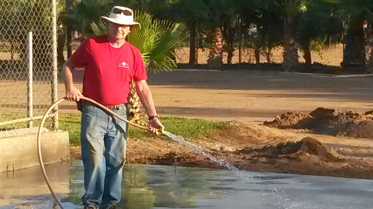 Rich watering down the fresh concrete so that it dries properly