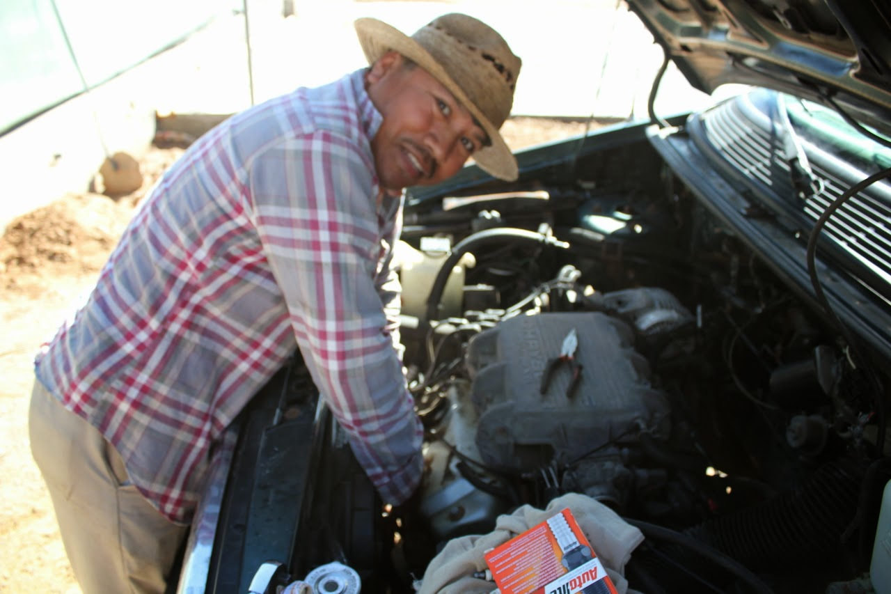 Isaias, the maintenance manager, changing spark plugs on the minivan.